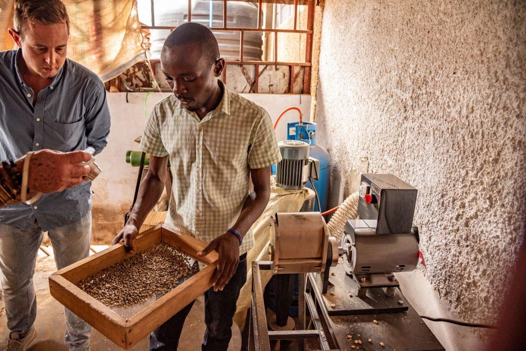 Im Bild prüft ein Mitarbeiter der Kooperative die Qualität des Kaffees mit einem großen Sieb, welches die Größe der Bohnen anzeigt. Daneben steht Thomas Angerer, der Reisebegleiter von life Earth Reisen. Das Foto ist bei der Kaffee Reise 2019 nach Uganda, beim Besuch der Bio Fairtrade Kaffee Bauern und der Betriebsbesichtigung der Bio Fairtrade Kaffee Kooperative entstanden. Wir führen durch alle Schritte der Kaffeeernte und –Produktion. Sie sehen die Qualitätskontrolle der Kaffeebohnen.