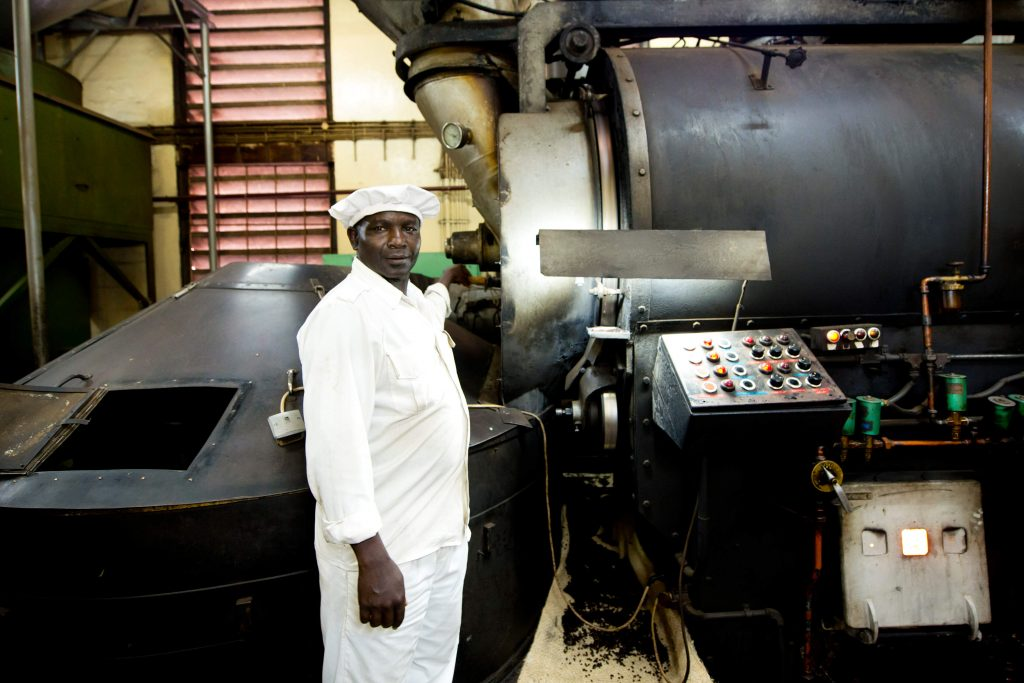 Das Foto zeigt einen Mitarbeiter im Vordergrund. Im Hintergrund sehen Sie die Kaffeeröstung. Das Foto ist bei der Kaffee Reise beim Besuch der Bio Fairtrade Kaffee und der Betriebsbesichtigung der Bio Fairtrade Kaffee Kooperative Bauern in Tansania entstanden. Wir führen durch alle Schritte der Kaffee Herstellung. Sie sehen das Rösten der Kaffeebohnen.